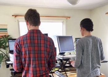 Two-people-stand-at-a-desk-with-their-backs-to-the-camera-in-a-small-room