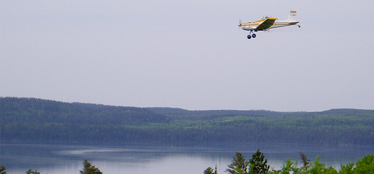 Crop duster flying over freshwater lake spraying into it