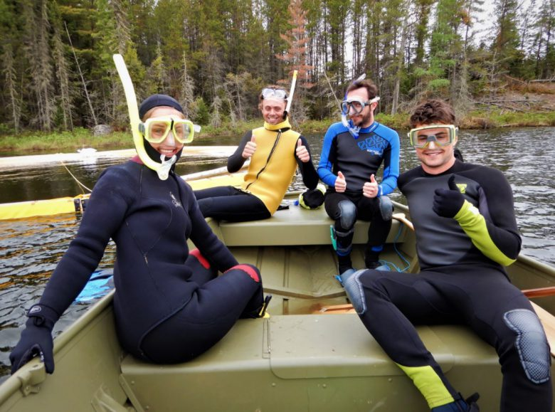 Four people sit on a boat with black and yellow scubadiving equipment