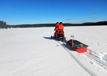 Two people snowmobile across a frozen lake