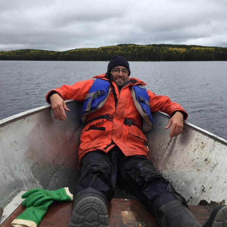 Artist Todd Stewart in a boat at IISD-ELA