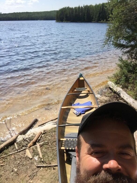 Matt Foster with a canoe by a lake at ELA