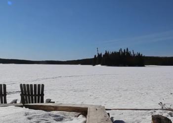 Three deck chairs overlooking frozen lake under blue skies Canada