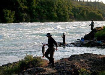 man next to lake holding fish