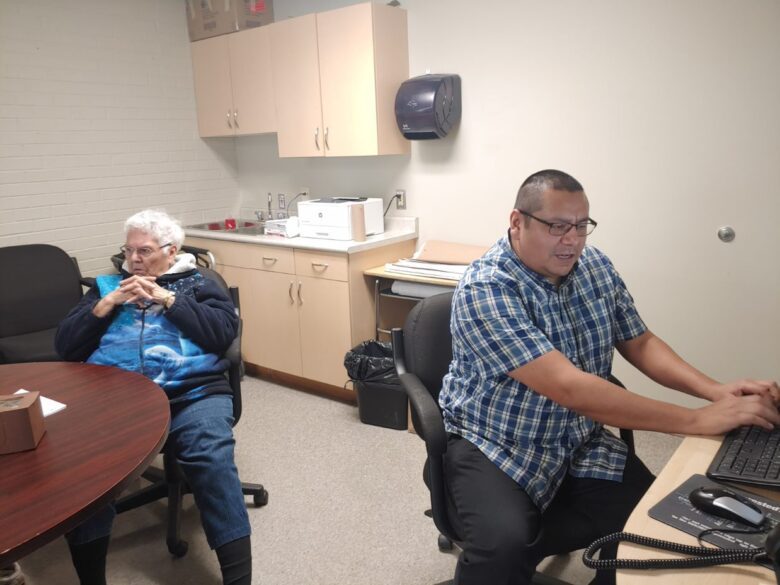 Two people sit at desks in from of computers in a room